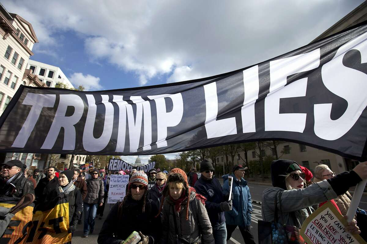 Demonstrators march on Pennsylvania Avenue protesting against climate policies and to impeach President Donald Trump, in Washington, Friday, Nov. 8, 2019. (AP Photo/Jose Luis Magana)