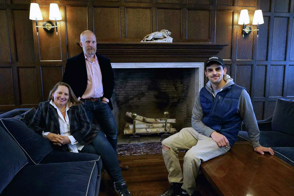 Co-owners of the Argus Hotel, Terra Stratton, left, and Matthew Smith, second from left, pose with Evan Hurry, owner of Capital Home Rennovation.com, at the hotel on Monday, Nov. 18, 2019, in Albany, N.Y. Hurry rebuilt the fireplace, seen in the background, with re-claimed material from within the building. (Paul Buckowski/Times Union)