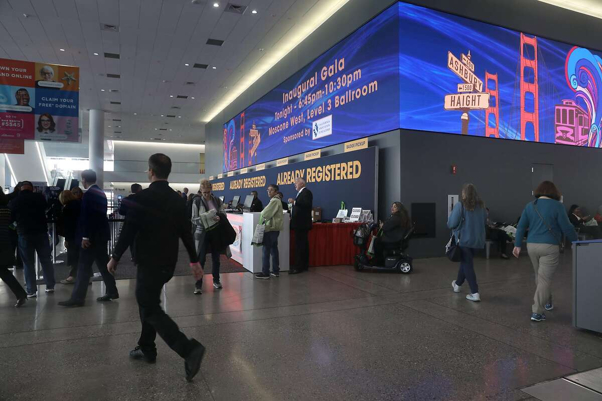 Attendees pick up their badges for the 2019 Realtors Conference & Expo at Moscone Center south on Thursday, Nov. 7, 2019, in San Francisco, Calif., where monitors now expand more of the lengths of the upper wall.