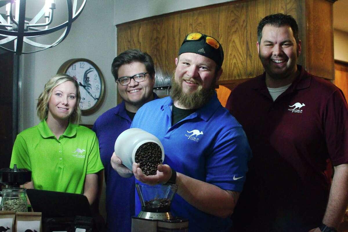 Fair Dinkum Coffee Co. President Chris Clark holds freshly roasted coffee beans. Partners in the nonprofit Deer Park online company are Stacye Hughes, left, Jonathan Clark and John Sheffield.