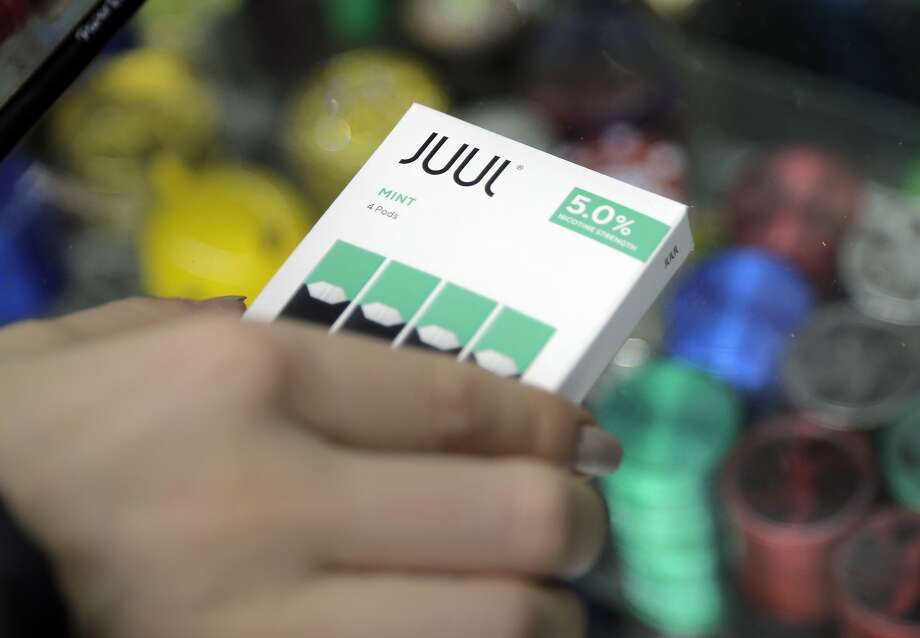 A woman buys refills for her Juul at a smoke shop in New York. The company's founders used a $12.8 billion investment from Altria Group Inc. to enrich themselves, a minority shareholder claims in a lawsuit. Photo: Seth Wenig / Associated Press 2018