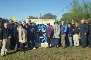 Kirby city officials are joined by city firefighters and police officers Friday at the unveiling of the city's first entry signage, along FM 78 near the city limits.