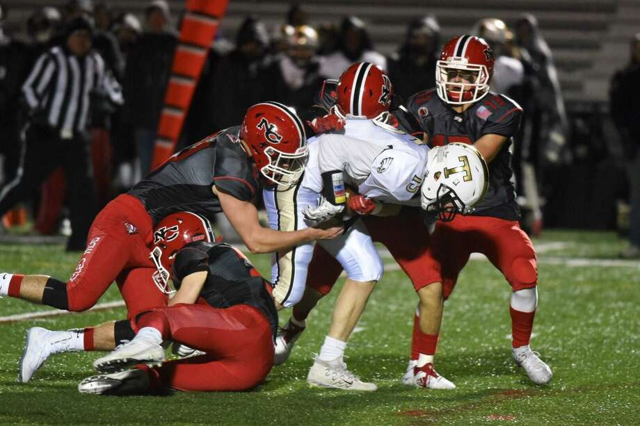 The New Canaan defense, including Braden Sweeney (91), Nick Gilio (5) and Walker Swindell (13) stop Trumbull's Kyle Atherton (15) after a catch during a football game at Dunning Field on Friday, Nov. 8, 2019. Photo: David Stewart / Hearst Connecticut Media / Connecticut Post