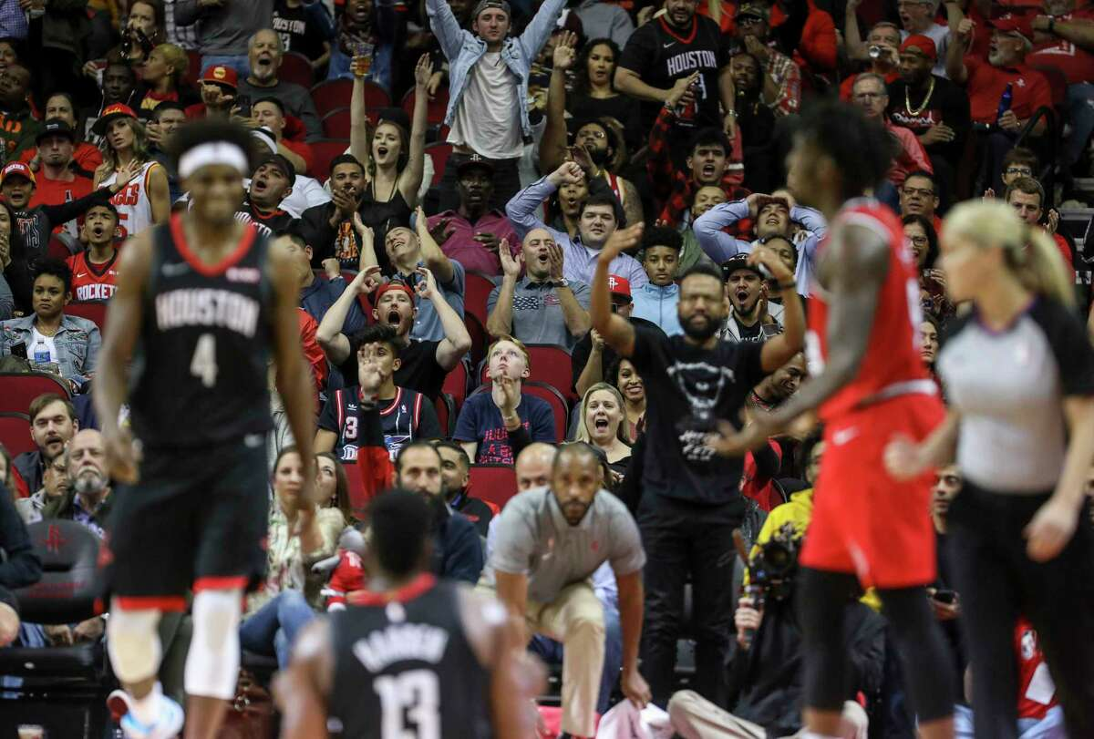 Fans react after Houston Rockets guard James Harden (13) made a three-point shot during the second quarter of an NBA basketball game at the Toyota Center on Monday, Nov. 18, 2019, in Houston.