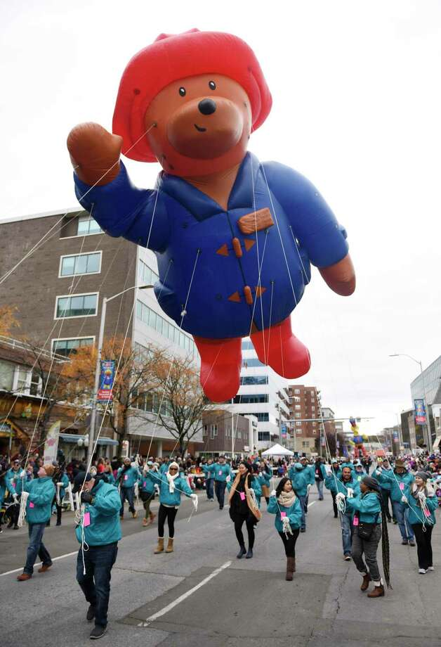 Carried by First County Bank employees, Paddington Bear waves to the crowd at the Stamford Downtown Parade Spectacular helium balloon parade in Stamford, Conn. Sunday, Nov. 18, 2018. Thousands attended the parade featuring 13 gigantic inflatable balloon characters, marching bands, fun floats, and Mr. and Mrs. Claus at the end, Photo: Tyler Sizemore / Hearst Connecticut Media / Greenwich Time