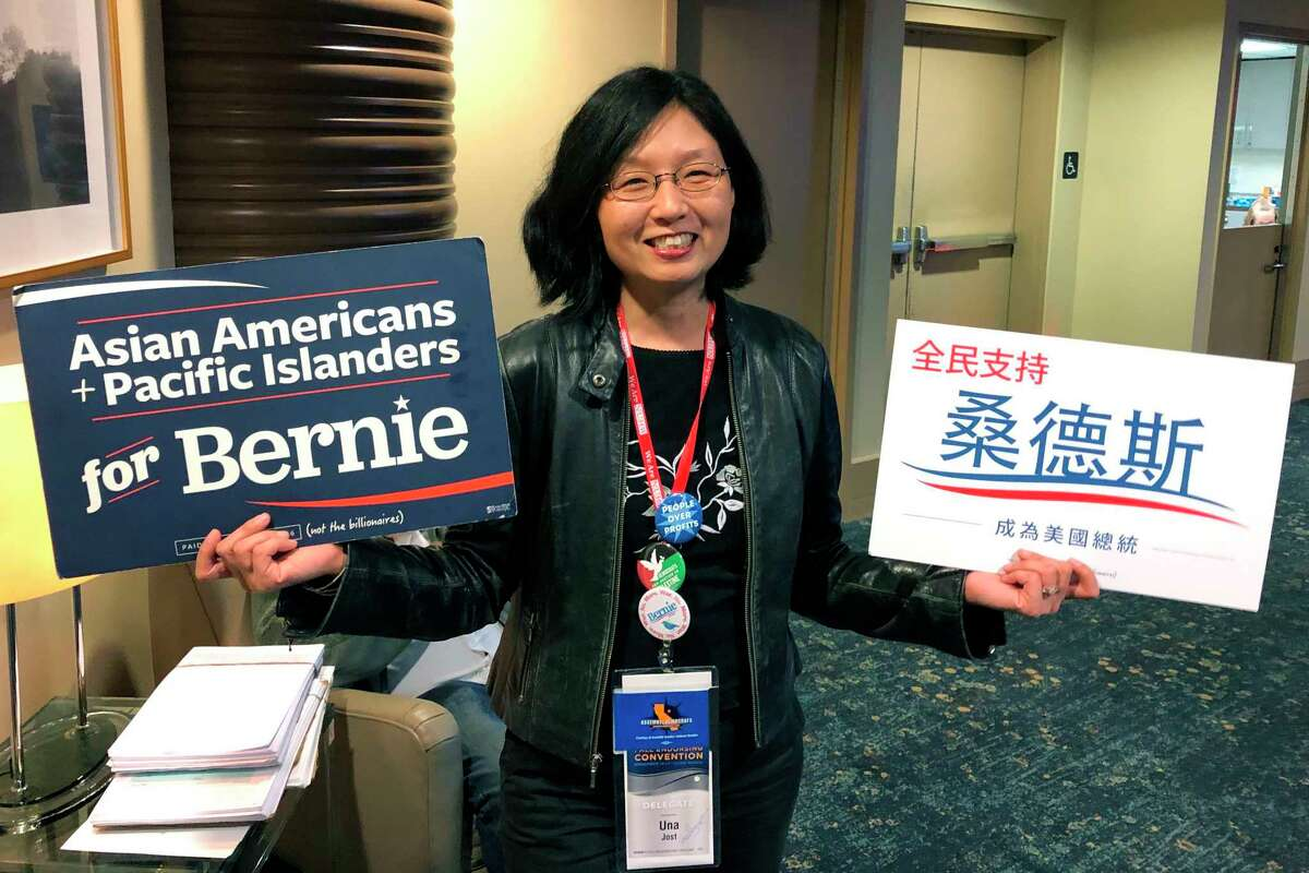 Una Lee Jost, a lawyer from Pasadena, Calif., holds signs supporting Bernie Sanders at the California Democratic Convention in Long Beach, Calif., Saturday, Nov. 16, 2019. She says any delay in a€œMedicare for Alla€ is a a€œserious concerna€ after Sen. Elizabeth Warren announced that getting Congress to pass a fully government-funded, universal health coverage plan would likely not come until the third year of her administration. (AP Photo/Michael R. Blood)
