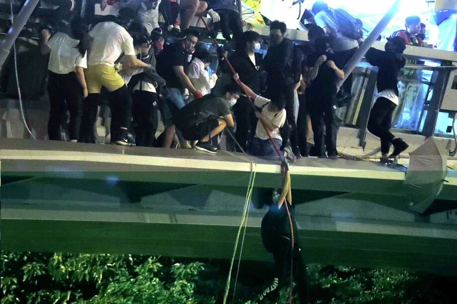Protestors use a rope to lower themselves from a pedestrian bridge to waiting motorbikes in order to escape from Hong Kong Polytechnic University and the police in Hong Kong, Monday, Nov. 18, 2019. As night fell in Hong Kong, police tightened a siege Monday at a university campus as hundreds of anti-government protesters trapped inside sought to escape. (AP Photo/Kin Cheung) Photo: Kin Cheung / Copyright 2019 The Associated Press. All rights reserved