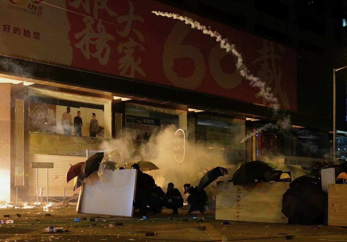 Protesters cover with umbrella as Police fire tear gas in the Kowloon area of Hong Kong, Monday, Nov. 18, 2019. As night fell in Hong Kong, police tightened a siege Monday at a university campus as hundreds of anti-government protesters trapped inside sought to escape. (AP Photo/Vincent Yu)