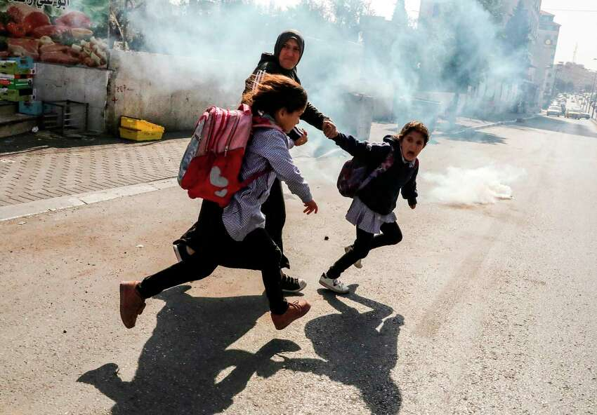 TOPSHOT - A woman and two school girls attempt to flee from tear gas fired at Palestinian journalists (unseen) gathering for a demonstration demonstration by Israel's controversial separation barrier in Bethlehem in the occupied West Bank on November 17, 2019, in solidarity with Palestinian cameraman Mu'ath Amarneh, who days before was injured in his eye by a rubber bullet while covering clashes between Palestinian protesters and Israeli security forces in a West Bank demonstration. - Israeli border police on November 15 had clashed with stone-throwing Palestinians protesting Israeli land confiscation in the village of Surif, northwest of Hebron, firing rubber bullets, one of which hit the news cameraman in the face, an AFP photographer who witnessed the injury said. Amarneh, who works for a local news agency, was taken to a hospital in Hebron. (Photo by HAZEM BADER / AFP) (Photo by HAZEM BADER/AFP via Getty Images)