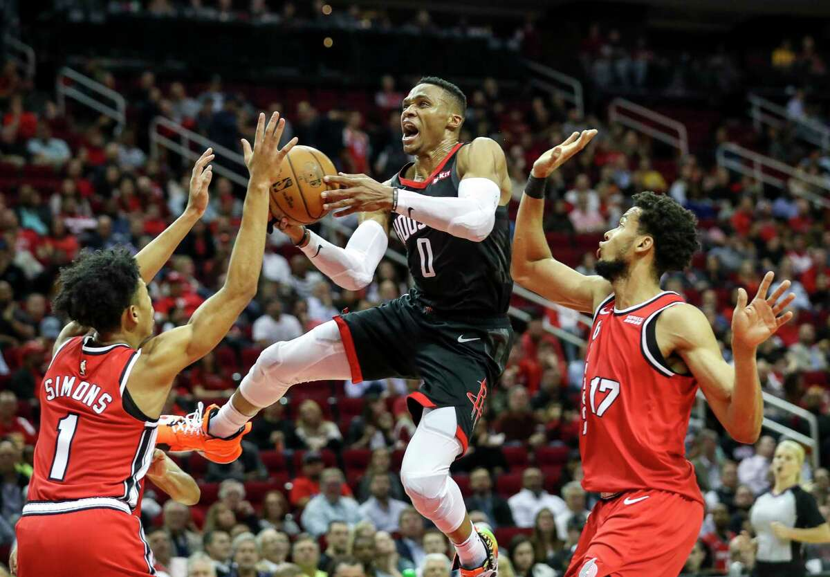 Rockets guard Russell Westbrook (0) drives to the basket past Trail Blazers guard Anfernee Simons (1) and forward Skal Labissiere (17) during the fourth quarter Monday at Toyota Center.