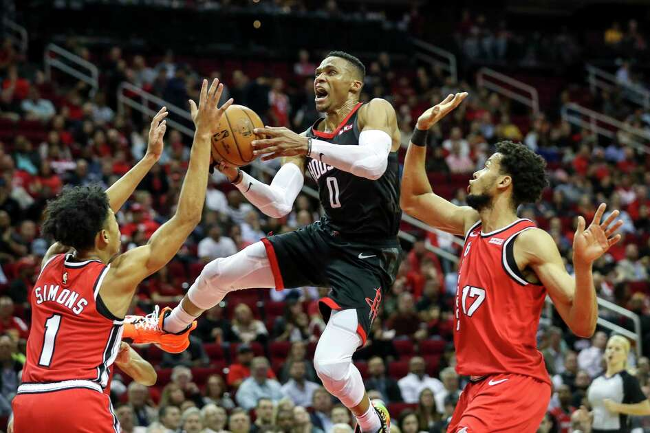 Houston Rockets guard Russell Westbrook (0) drives to the basket past Portland Trail Blazers guard Anfernee Simons (1) and forward Skal Labissiere (17) during the fourth quarter of an NBA basketball game at the Toyota Center on Monday, Nov. 18, 2019, in Houston.