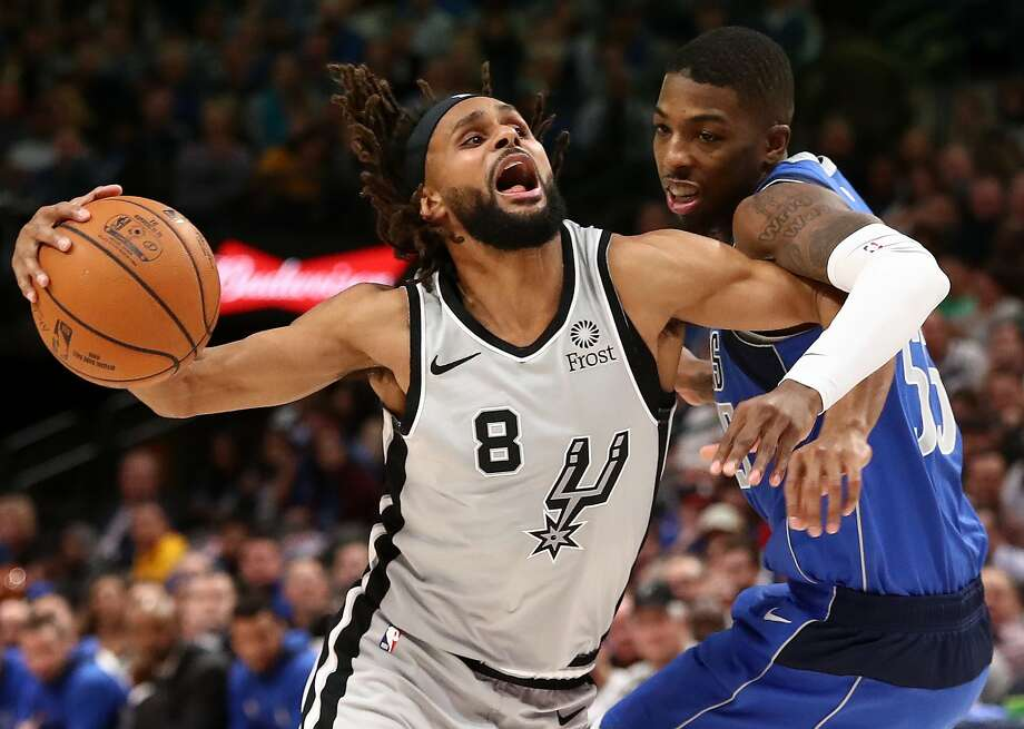 DALLAS, TEXAS - NOVEMBER 18:  Patty Mills #8 of the San Antonio Spurs is fouled by Delon Wright #55 of the Dallas Mavericks in the second half at American Airlines Center on November 18, 2019 in Dallas, Texas.  NOTE TO USER: User expressly acknowledges and agrees that, by downloading and or using this photograph, User is consenting to the terms and conditions of the Getty Images License Agreement. (Photo by Ronald Martinez/Getty Images) Photo: Ronald Martinez, Getty Images