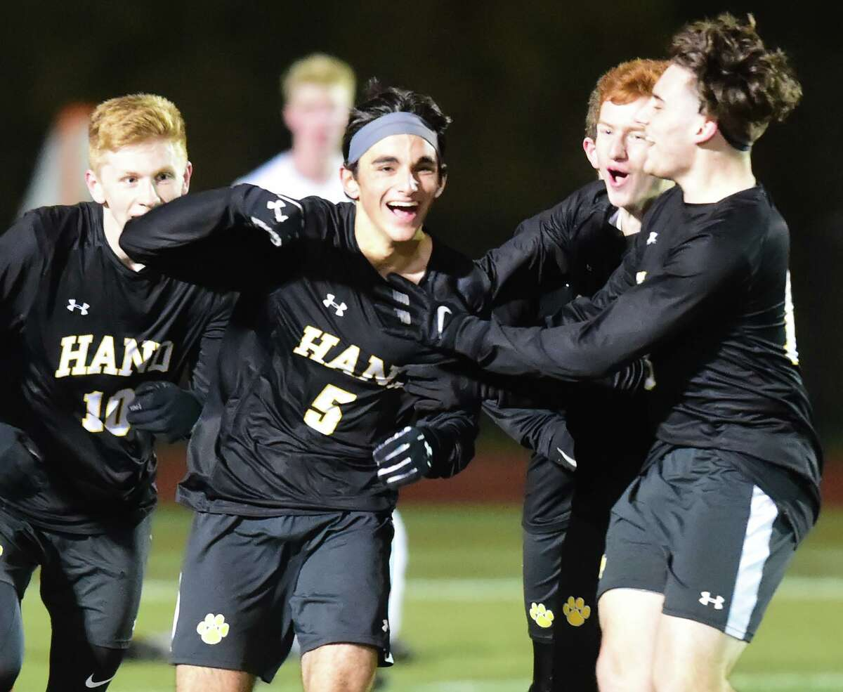 Hand's Matthew Luongo (5) celebrates with teammates against Guilford in the Class L state semifinals on Monday.
