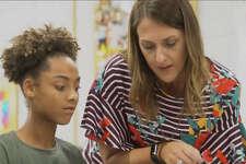 Lewis & Clark Jr. High School teacher Tiffany Falk looks over a student's work.