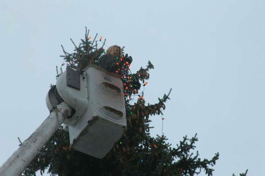 Workers decorate a 66 foot evergreen which overlooksdowntown Bear Lake. Approximately 1,400 lightssupplied by the Bear Lake Promoters are strung up each year. (Scott Fraley/News Advocate)