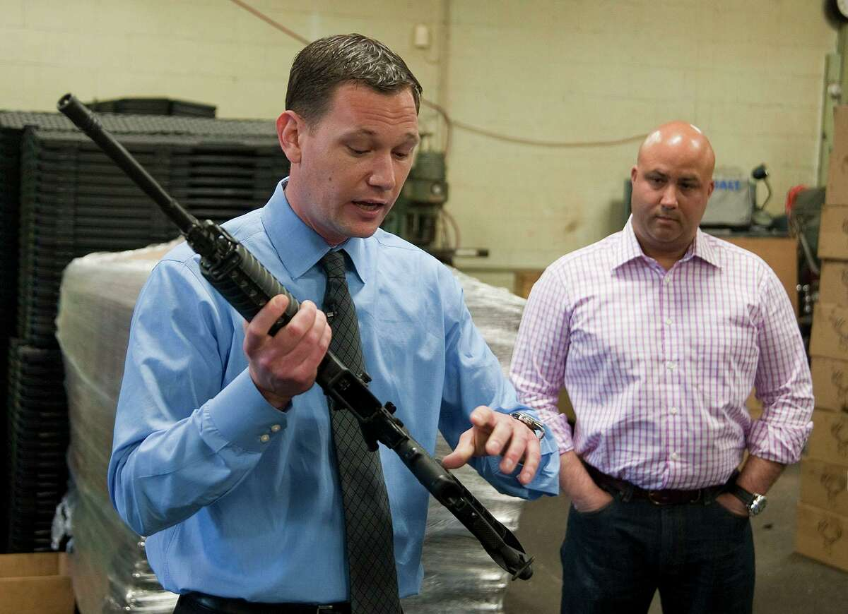 Mark Malkowski, owner of Stag Arms in New Britain, Conn. talks about his company's newly designed Stag-22, a weapon he says will be legal in the state of Connecticut, during a news conference on Thursday May 9, 2013. Looking on is John A. Napierski, Jr., owner of Jojo's Gun Works LLC in Southington, Conn. Malkowski says the reworked rifle should be legal because it uses a lower caliber bullet than the traditional AR-15, but the company was consulting police before going into production. Gun control advocates say the move violates the spirit of the new law, which expands Connecticut's assault weapons ban and bans large capacity ammunition magazines. (AP Photo/The Republican-American, Jim Shannon)