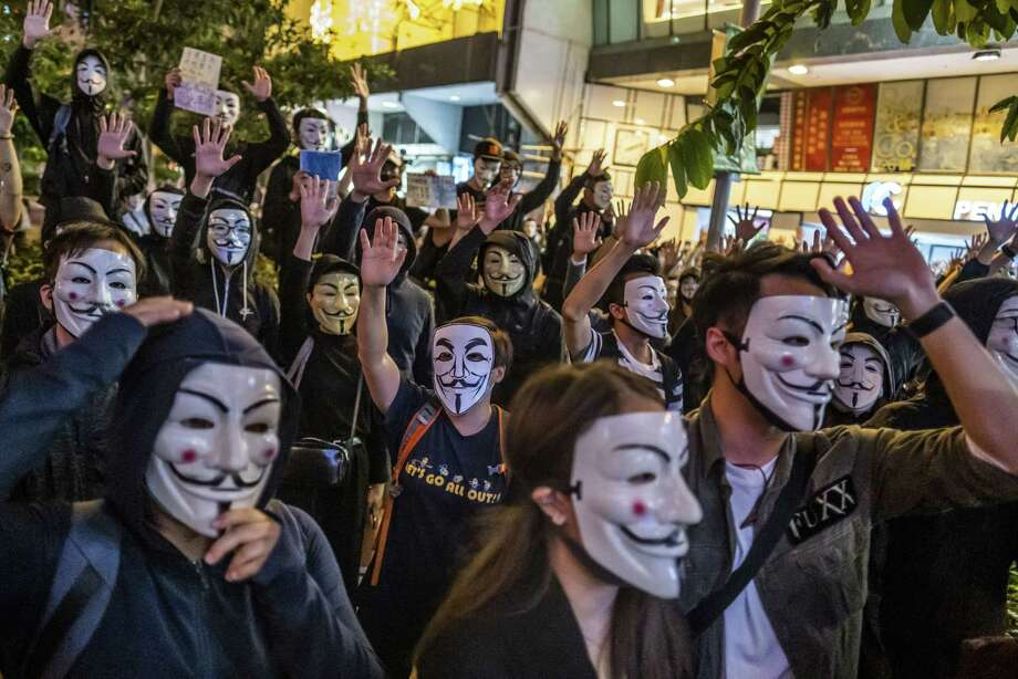 Demonstrators wearing anonymous masks known as Guy Fawkes masks raise their hands during a protest at Urban Council Centenary Garden in Hong Kong on Nov. 5, 2019. Photo: Bloomberg Photo By Justin Chin / Bloomberg