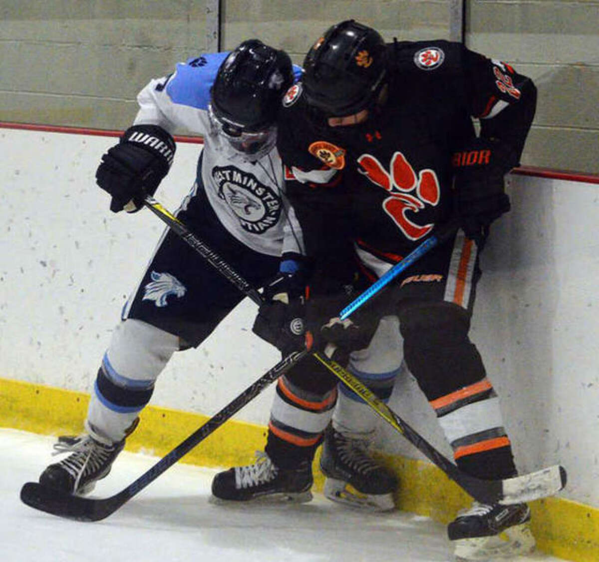 Edwardsville senior Trevor Laub, right, battles for the puck during Friday's game against Westminster at Queeny Recreational Complex.