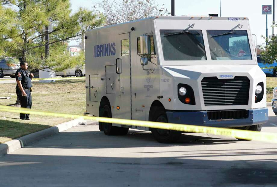 Law enforcement investigate the scene after two men attempted to rob a Brinks security employee while servicing an ATM at a Chase bank, Tuesday, Nov. 19, 2019, in Willis. The employee shot and killed one suspect, while law enforcement is searching for the other who fled. Photo: Jason Fochtman, Staff Photographer / Houston Chronicle