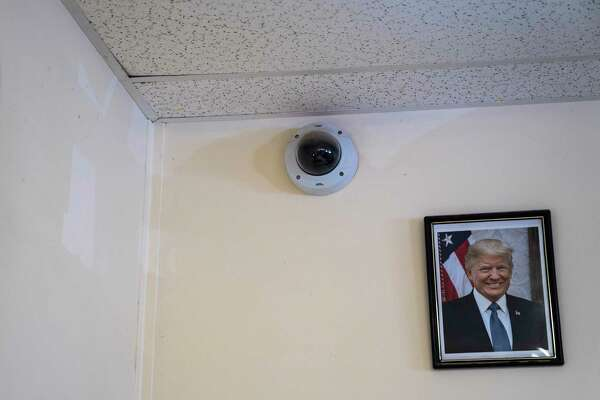 A security camera and portrait of President Donald Trump inside a security booth at the South Texas Family Residential Center, a U.S. Immigration and Customs Enforcement facility that houses families who are pending disposition of their cases, in Dilley, Texas.