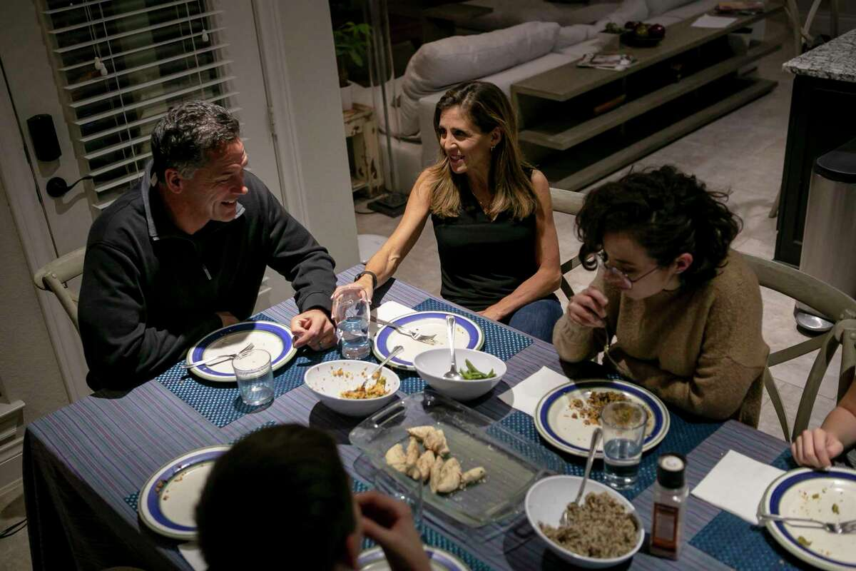 Nusha Bladinieres talks to her husband Jan Michell as they eat dinner with Nusha's children in their home in New Braunfels.