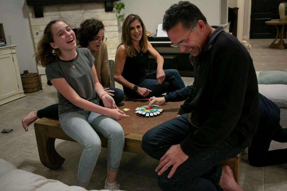 Laughter erupts at the end of a round of a game in the Michell family home.