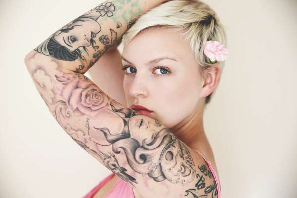 Heavily tattooed woman wearing a flower in her hair.