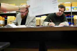 Patrick Nelson, left, vice-chair of the Stillwater Democratic Party, and Scott Kingsley, right, with the Saratoga County Republican Committee mark down votes on pieces of paper to keep count as they are shown an absentee ballot on Tuesday, Nov. 19, 2019 in Ballston Spa, N.Y. Absentee ballots were being counted in the Stillwater Town Council race between Lisa Bruno and Valerie Masterson. (Paul Buckowski/Times Union)