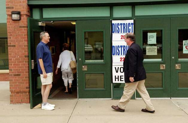Volunteer greeter Frank Troise welcomes and directs voters at Scofield Middle School in Stamford, Conn. on Tuesday August 10, 2010. Photo: Dru Nadler / Stamford Advocate