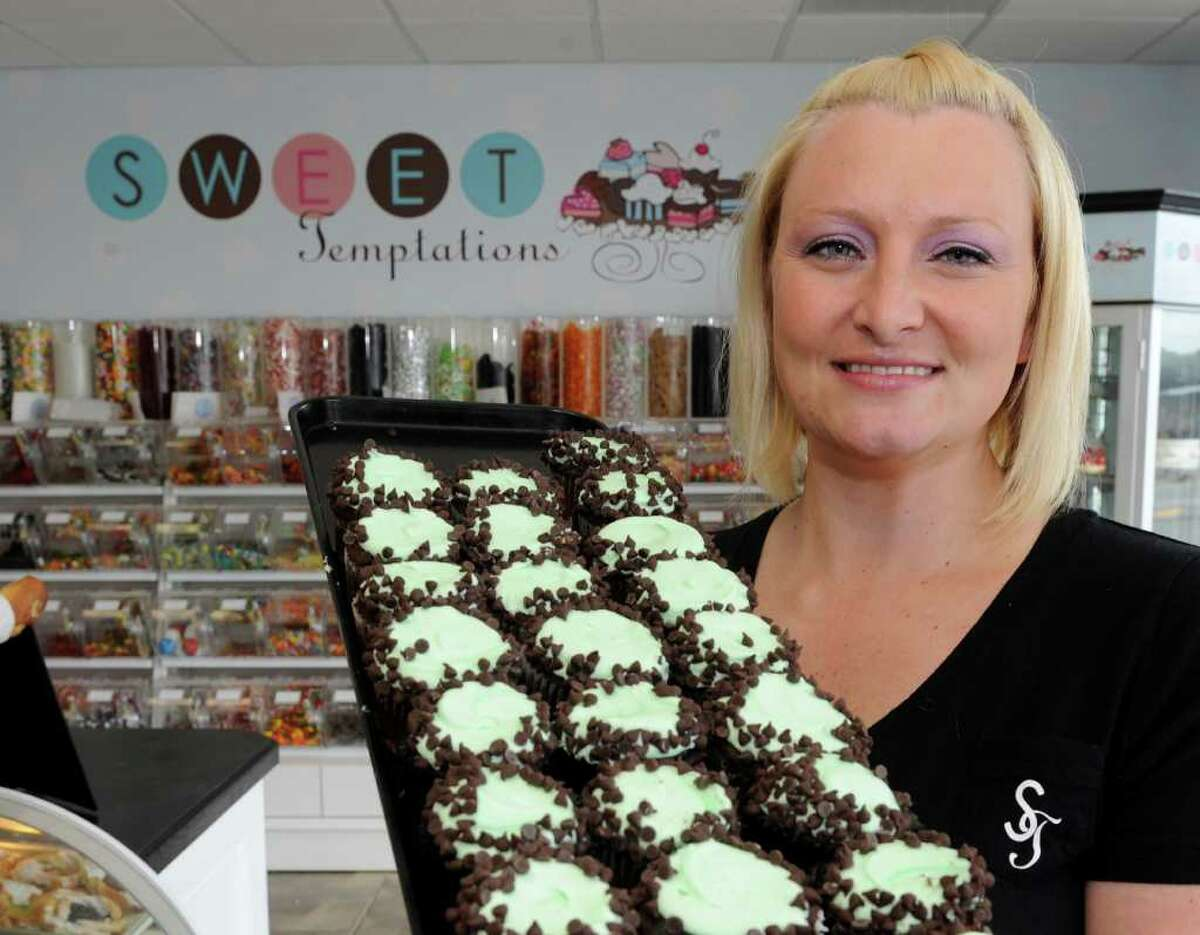 Nina Crisafulli shows off some of her cupcakes at Sweet Temptations in Colonie on Tuesday. Her business is among four bakeries accused of violating Albany County's ban on trans fat. (Skip Dickstein/Times Union)