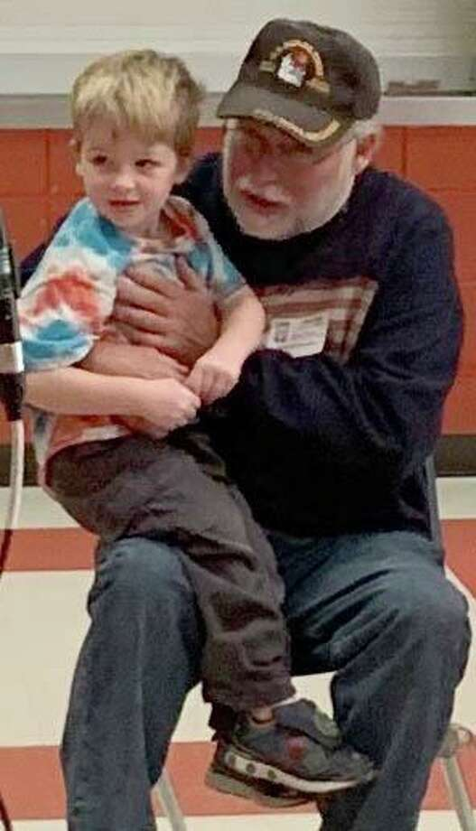 Ben Laughlin, a preschooler in Marley Koschel's class, sits atop the lap of his grandfather, veteran Mike Trosan, during the ceremony. Photo: Courtesy Of Northville Elementary School / The News-Times Contributed
