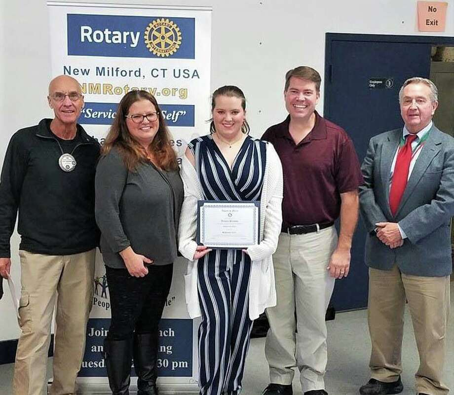 The Rotary Club of New Milford recently presented its September Student of the Month Award to Aurora Preusse. A senior at NMHS, Aurora has been goalie for the varsity field hockey team, a teacher's assistant in woodworking class, a member of NMHS chorus and worked on the NMHS musical scenery. She has a special interest in German history, language and culture. She plans to attend college and pursue a career in forensic psychology. Aurora, center, is shown above with, from left to right, Rotarian Tom McSherry, Aurora's parents, Carolin Preusse and Kevin Preusse, and NMHS teacher, James R. Wilson. Photo: Courtesy Of Rotary Club Of New Milford / The News-Times Contributed