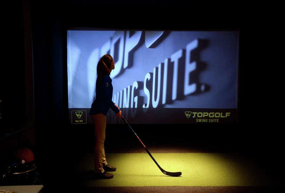 An employee tests out her stance as she awaits pre-opening customers in the Topgulf Swing Suite at 5 Under Golf, a new Topgolf and Toptracer venue with bar and restaurant, which will have a soft opening Thursday and remain open for individual reservations, private parties and more. Construction continues on the outdoor portion of the facility, formerly Games People Play on College Street,, with a grand opening expected to take place in March.  Photo taken Tuesday, November 19, 2019 Kim Brent/The Enterprise Photo: Kim Brent / The Enterprise / BEN