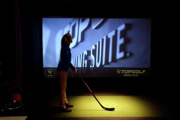 An employee tests out her stance as she awaits pre-opening customers in the Topgulf Swing Suite at 5 Under Golf, a new Topgolf and Toptracer venue with bar and restaurant, which will have a soft opening Thursday and remain open for individual reservations, private parties and more. Construction continues on the outdoor portion of the facility, formerly Games People Play on College Street,, with a grand opening expected to take place in March. Photo taken Tuesday, November 19, 2019 Kim Brent/The Enterprise
