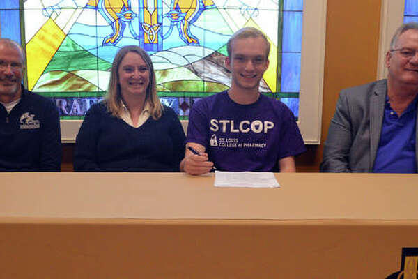 Father McGivney senior Zach Brasel, second from right, will compete in cross country and track and field at St. Louis College of Pharmacy. He is joined by his parents and FMCHS coach Jim Helton.