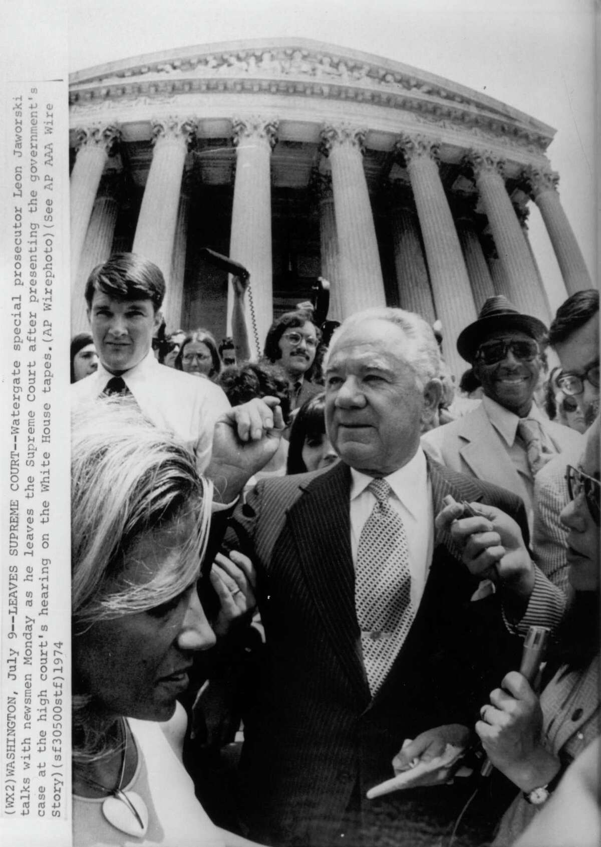 Watergate Special Prosecutor Leon Jaworski talks with reporters as he leaves the Supreme Court after presenting the government's case at the high court's hearing on the White House tapes.