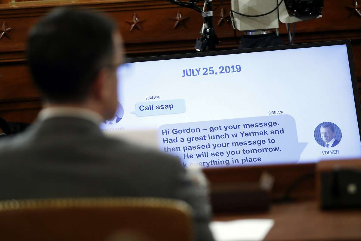A text message to Gordon Sondland from Tim Morrison, left, a former official at the National Security Council, is displayed during the House Intelligence Committee on Capitol Hill in Washington, Tuesday, Nov. 19, 2019, during a public impeachment hearing of President Donald Trump's efforts to tie U.S. aid for Ukraine to investigations of his political opponents. (AP Photo/Jacquelyn Martin, Pool)