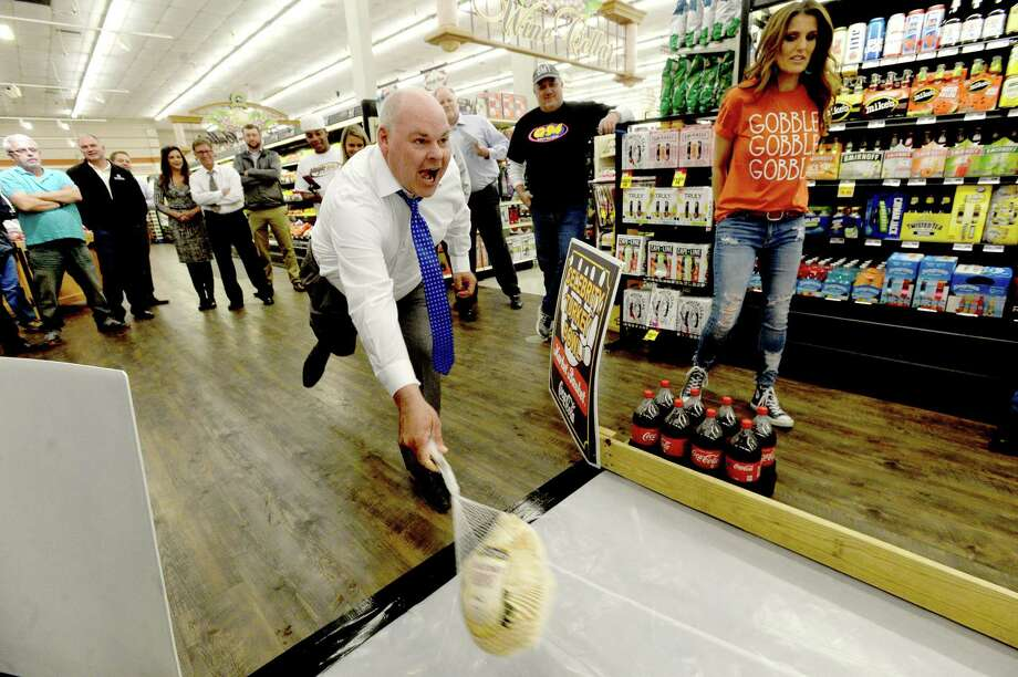 Tracy Kennick looks on as KJAC's Jeff Gerber sends another frozen turkey flying down the lane during the 2nd annual Celebrity Turkey Bowl Tuesday at the Market Basket on Phelan Road in Beaumont. Teams from various local media joined in the event, each bowling with turkeys to raise money for local charitable organizations. Photo taken Tuesday, November 19, 2019 Kim Brent/The Enterprise Photo: Kim Brent / The Enterprise / BEN