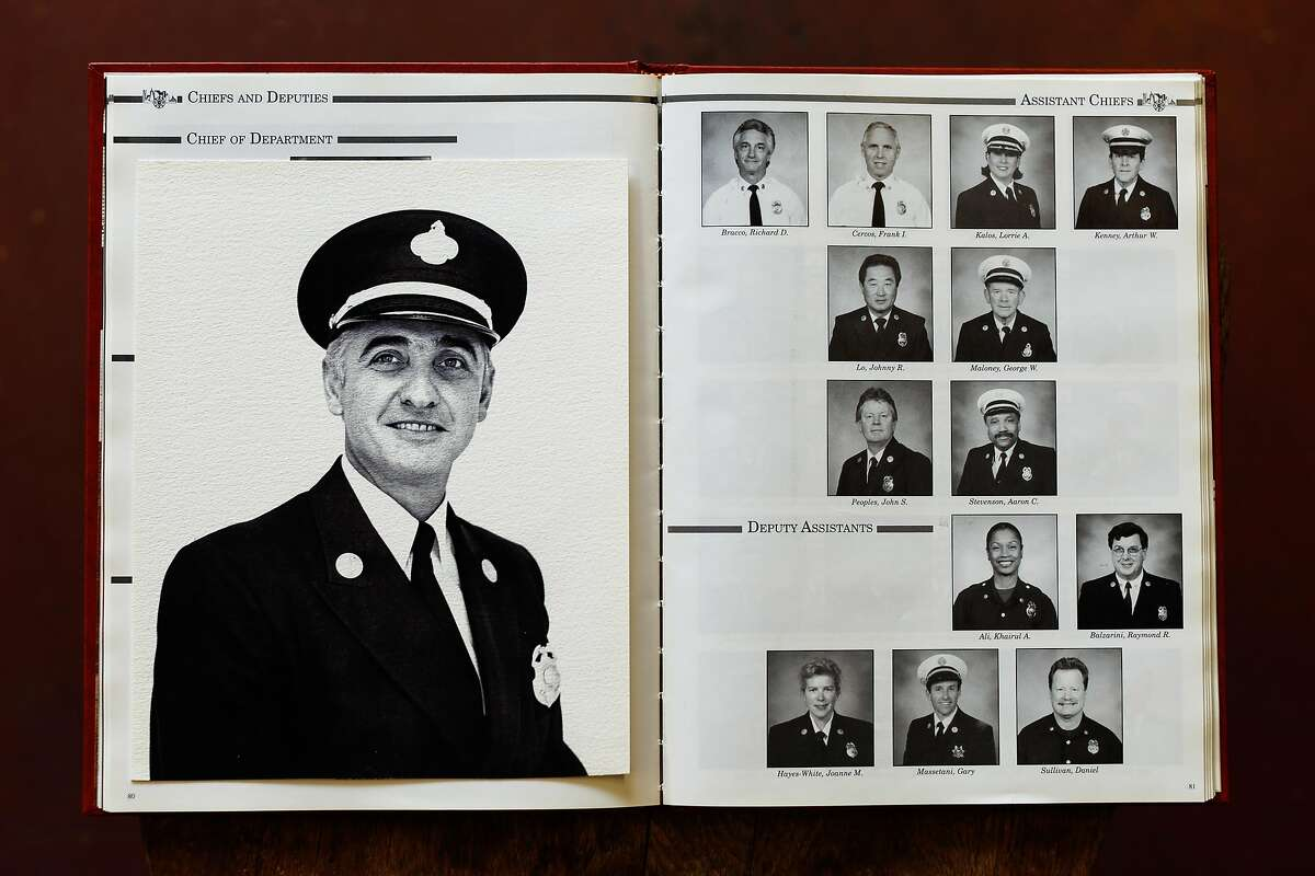 SFFD Yearbook from 1997 at Fire Station No. 38 on Thursday, Nov. 14, 2019, in San Francisco, Calif. The photograph placed on the left side of the book is a portrait of Firefighter Chief Frank Cercos IV grandfather. The second photo of the first line on the right side of the book is a portrait of his father.