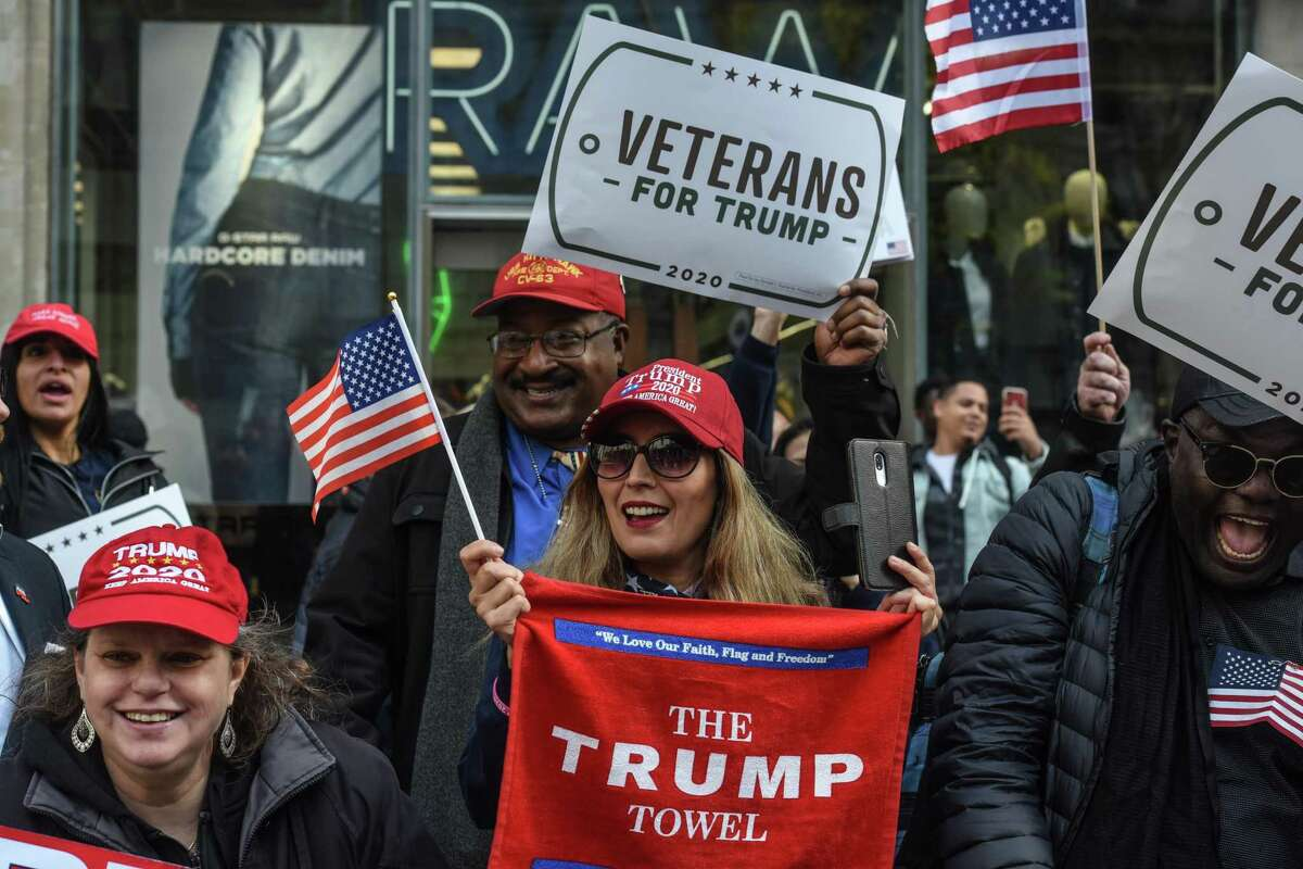 Trump supporters hold signs on the sidelines during the Veterans Day parade on Nov. 11, in New York City. By signing the VA Mission Act, Trump has kept his promise to U.S. veterans.