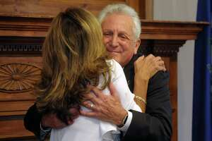 Mayor Harry Rilling hugs his wife Lucia after being sworn in for his fourth term as mayor at Norwalk City Hall, in Norwalk, Conn. Nov. 19, 2019.