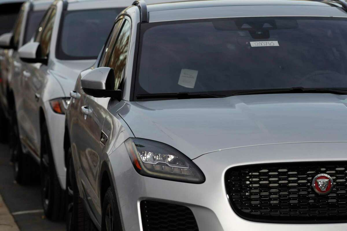 In this Sunday, Nov. 10, 2019, photograph, a long row of unsold 2020 E-Pace sports-utility vehicles sits at a Jaguar dealership in Littleton, Colo. (AP Photo/David Zalubowski)