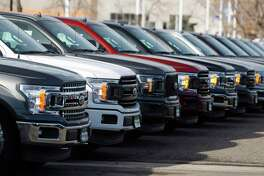 In this Sunday, Nov. 10, 2019, photograph, a long row of unsold 2020 F-150 pickup trucks sits at a Ford dealership in Littleton, Colo. (AP Photo/David Zalubowski)