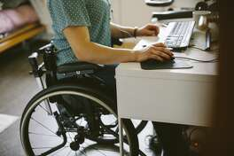 Midsection of young disabled woman using computer at home - stock photo