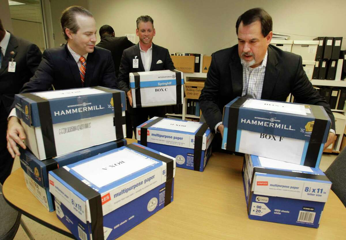 Jared Woodfill, left, David Welch, right, and others with a group seeking to repeal the HERO (Houston Equal Rights) ordinance delivers boxes of signatures to the office of Houston City Secretary Thursday, July 3, 2014. ( Melissa Phillip / Houston Chronicle )