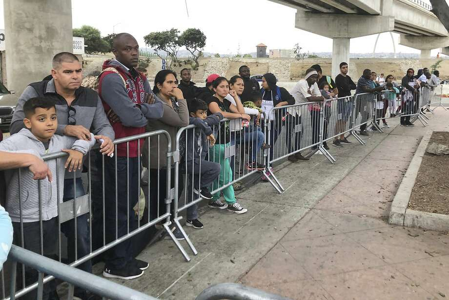 People wishing to apply for asylum wait at a border crossing in Tijuana near San Diego. A judge calls a U.S. policy toward some asylum seekers misleading. Photo: Elliot Spagat / Associated Press