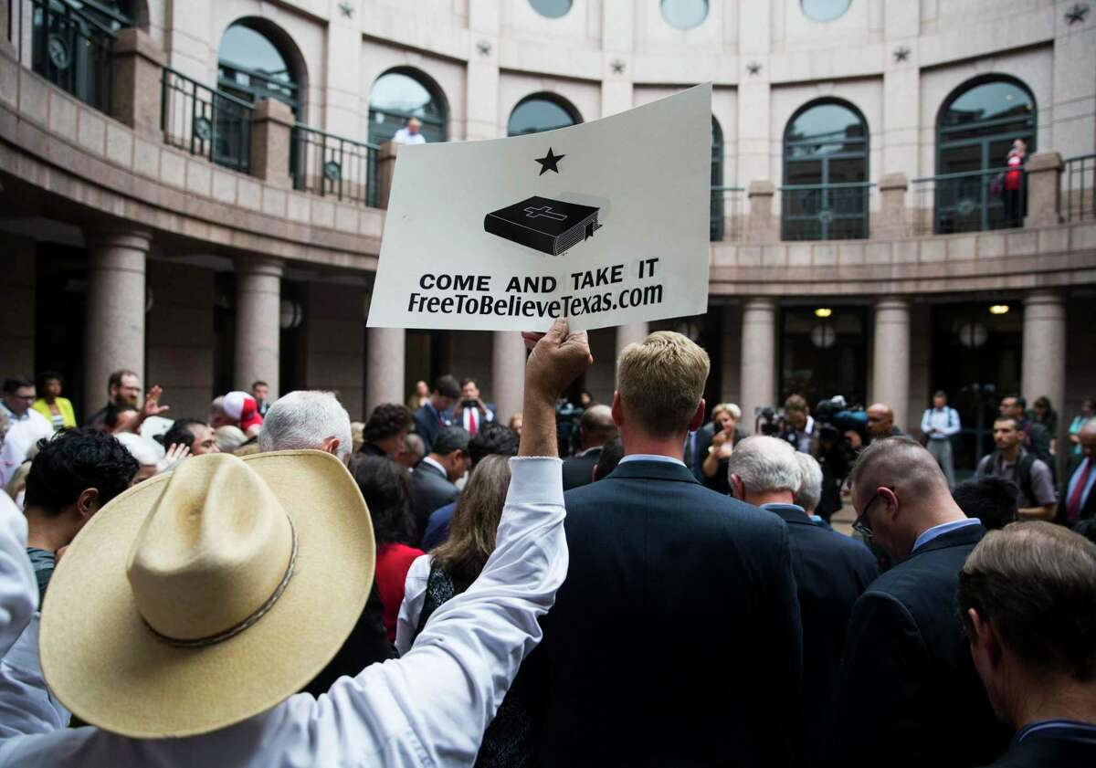 """A supporter holds up a sign during a press conference as part of """"Save Chick-fil-A Day"""" at the Texas State Capital extension on Wednesday, April 17, 2019 in Austin."""
