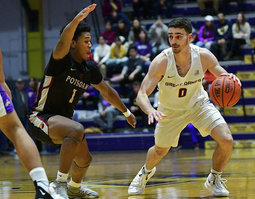 University at Albany's Antonio Rizzuto is defended by Potsdam's Jayquan Thomas during a basketball game at SEFCU Arena on Tuesday, Nov. 19, 2019 in Albany, N.Y. (Lori Van Buren/Times Union)