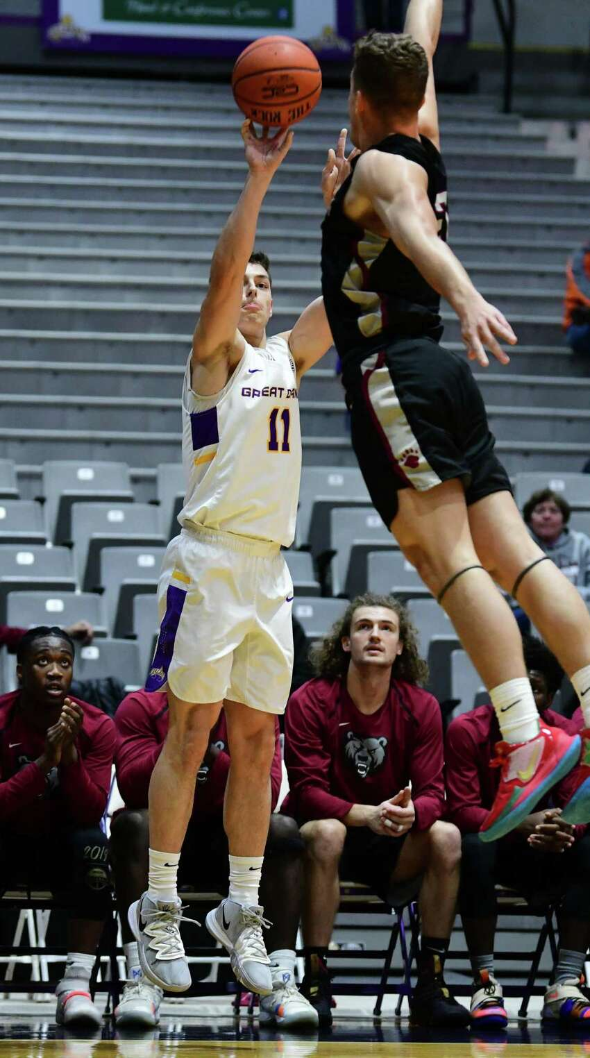 University at Albany's Cameron Healy puts down a three-pointer against Potsdam's Aaron Armstrong during a basketball game at SEFCU Arena on Tuesday, Nov. 19, 2019 in Albany, N.Y. (Lori Van Buren/Times Union)