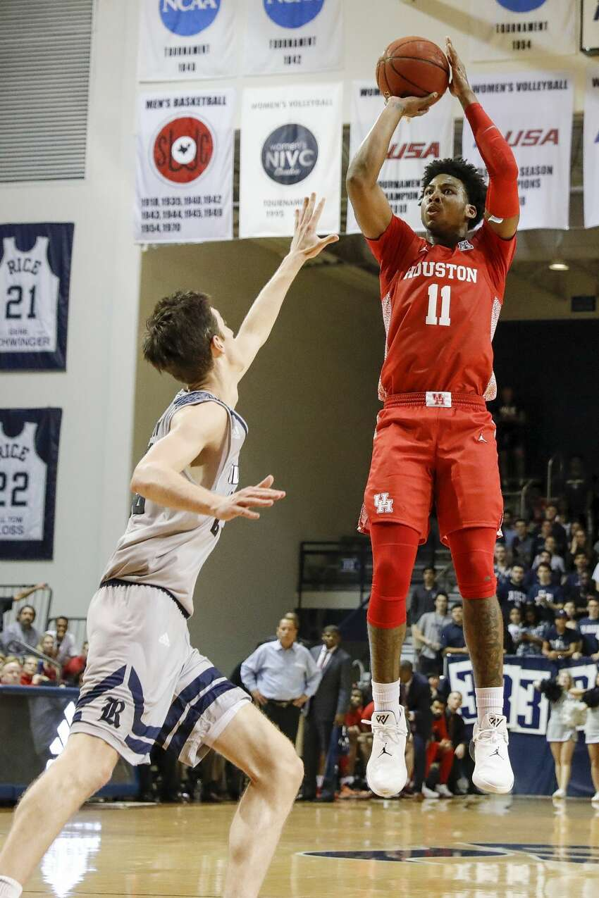 Houston Cougars guard Nate Hinton (11) takes a three point shot defended by Rice Owls guard Drew Peterson (23) during the first half of the NCAA basketball game between the Rice Owls and the Houston Cougars at Tudor Fieldhouse in Houston, TX on Tuesday, November 19, 2019. The Cougars defeated the Owls 97-89.